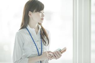 手帳と携帯電話を持つビジネスウーマンの写真素材 [FYI02508870]