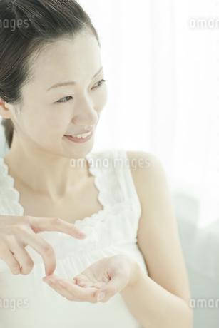 化粧水を手に取る女性 美容とスキンケアイメージの写真素材 [FYI02508904]