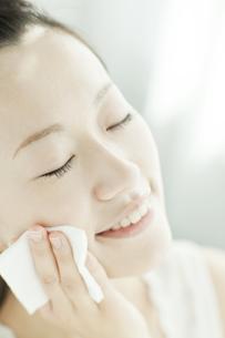 コットンを顔に置く女性 美容とスキンケアイメージの写真素材 [FYI02508927]