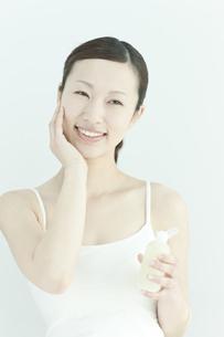 ローションを手に持つ若い女性のスキンケアイメージの写真素材 [FYI02508974]