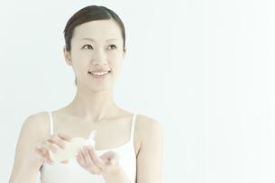 ローションを手に持つ若い女性のスキンケアイメージの写真素材 [FYI02509063]