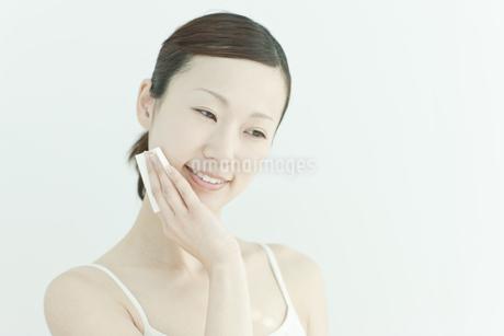コットンで顔をふく若い女性のスキンケアイメージの写真素材 [FYI02509118]