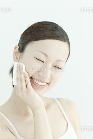 コットンで顔をふく若い女性のスキンケアイメージの写真素材 [FYI02509160]