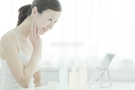 鏡を覗き込む女性のスキンケアイメージの写真素材 [FYI02509206]