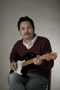 ギターを弾くシニア男性の写真素材 [FYI02509224]