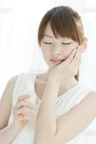 ローションを持つ若い女性の写真素材 [FYI02509255]