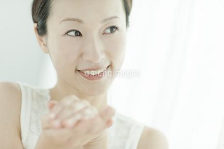 化粧水を手に取り暖める女性 美容とスキンケアイメージの写真素材 [FYI02509258]
