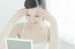 鏡を覗き込む女性のスキンケアイメージの写真素材 [FYI02509312]