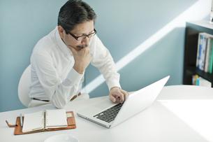 パソコンの前で考えるシニア男性の写真素材 [FYI02509313]
