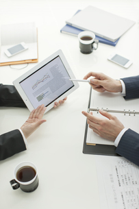 タブレットPCで打ち合せするビジネスマンとビジネスウーマンの写真素材 [FYI02509338]