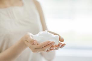 洗顔の泡を両手に持つスキンケアイメージの写真素材 [FYI02509390]