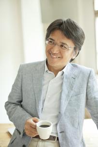コーヒーカップを持つミドル男性の写真素材 [FYI02509401]