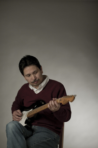 ギターを弾くシニア男性の写真素材 [FYI02509424]