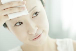 コットンを顔に置く女性 美容とスキンケアイメージの写真素材 [FYI02509474]
