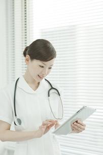 タブレットパソコンを操作する看護士の写真素材 [FYI02509519]