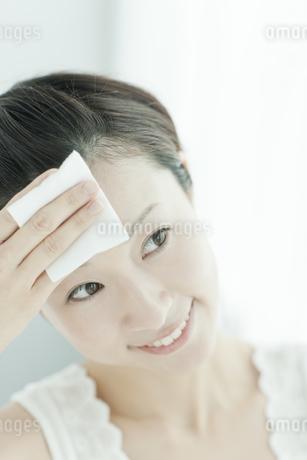 コットンを顔に置く女性 美容とスキンケアイメージの写真素材 [FYI02509520]