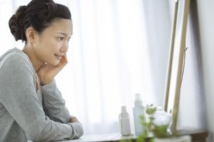 鏡を見る若い女性のスキンケアイメージの写真素材 [FYI02509549]