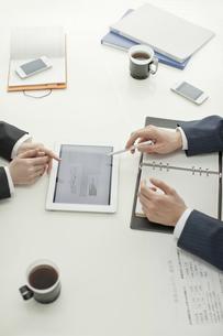 タブレットPCで打ち合せするビジネスマンとビジネスウーマンの写真素材 [FYI02509577]