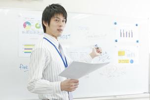 ホワイトボードを指し発言する男性社員の写真素材 [FYI02509601]