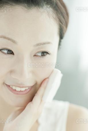 コットンを顔に置く女性 美容とスキンケアイメージの写真素材 [FYI02509627]