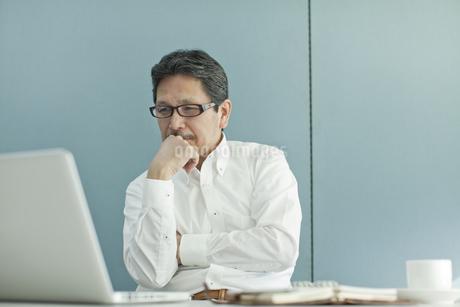 パソコンの前で考えるシニア男性の写真素材 [FYI02509632]