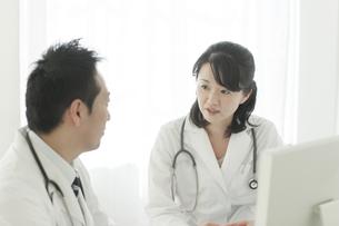 パソコンの前で話す2人の医師の写真素材 [FYI02509670]