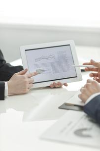 タブレットPCで打ち合せするビジネスマンとビジネスウーマンの写真素材 [FYI02509671]