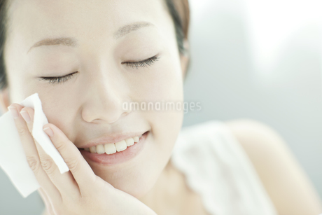 コットンを顔に置く女性 美容とスキンケアイメージの写真素材 [FYI02509740]