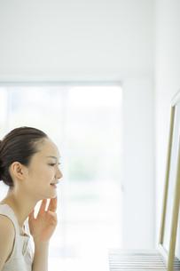 鏡を見て顔に手を触れるスキンケアイメージの写真素材 [FYI02509784]