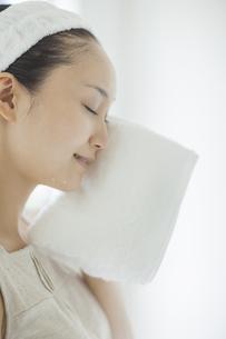 タオルで顔を拭くスキンケアイメージの写真素材 [FYI02509802]