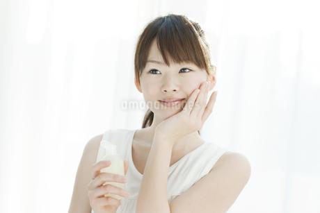 ローションを持つ若い女性の写真素材 [FYI02509862]
