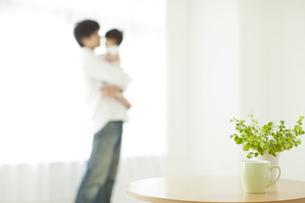 テーブルの向こうで赤ちゃんを抱っこする父親の写真素材 [FYI02509874]
