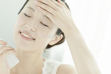 化粧水で顔にうるおいを与える女性 美容とスキンケアイメージの写真素材 [FYI02509885]