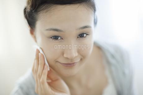 コットンを顔にあてるスキンケアイメージの写真素材 [FYI02509941]