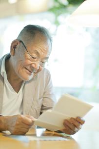 手紙を読むシニア男性の写真素材 [FYI02509946]
