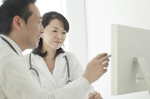 パソコンの前で話す2人の医師の写真素材 [FYI02509976]