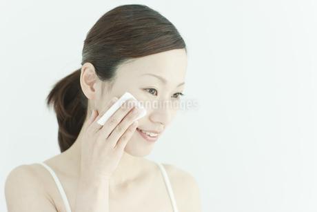 コットンで顔をふく若い女性のスキンケアイメージの写真素材 [FYI02510026]