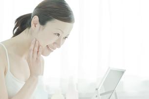 鏡を覗き込む女性のスキンケアイメージの写真素材 [FYI02510036]
