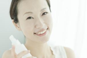 化粧水のボトルを持つ女性 美容とスキンケアイメージの写真素材 [FYI02510043]