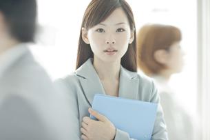 スーツ姿でファイルを持つビジネスウーマンの写真素材 [FYI02510084]