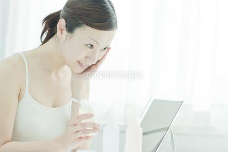 鏡の前でローションを手に持つ女性スキンケアイメージの写真素材 [FYI02510143]