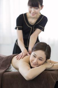 背中のオイルマッサージを受ける若い女性の写真素材 [FYI02510220]