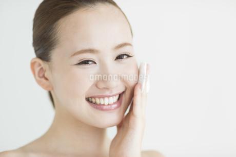 顔にコットンあてるスキンケアイメージの写真素材 [FYI02510499]
