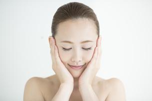 両手で顔を包み込む女性のスキンケアイメージの写真素材 [FYI02510531]