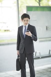 携帯電話を見るビジネスマンの写真素材 [FYI02510718]
