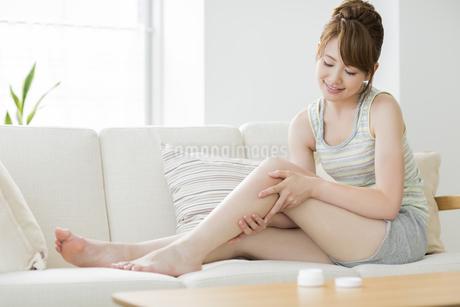 脚にクリームを塗る若い女性の写真素材 [FYI02510770]