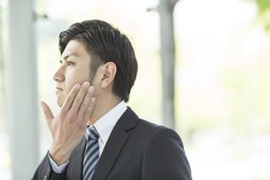 頬に手をあてるビジネスマンの写真素材 [FYI02510830]