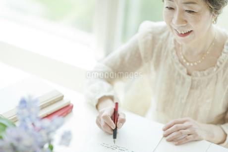 リビングで手紙を書く中高年女性の写真素材 [FYI02510865]