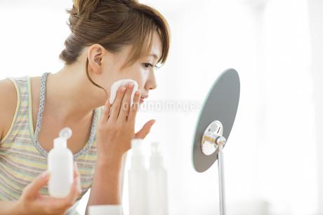 コットンを頬にあてて鏡を見る女性の写真素材 [FYI02510884]