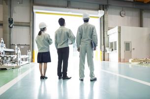 工場に立つ男女作業員の後姿の写真素材 [FYI02510950]